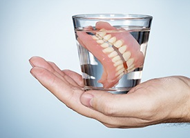 Glass filled with water and full denture