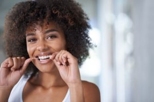 woman flossing to prevent gum disease during American Heart Month