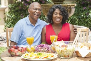elderly couple eating with dentures outside
